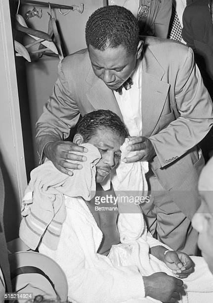 New York, NY- One of Sugar Ray Robinson's handlers wipes off the sweat and blood from the boxer's face in the dressing room after the 31-year-old...