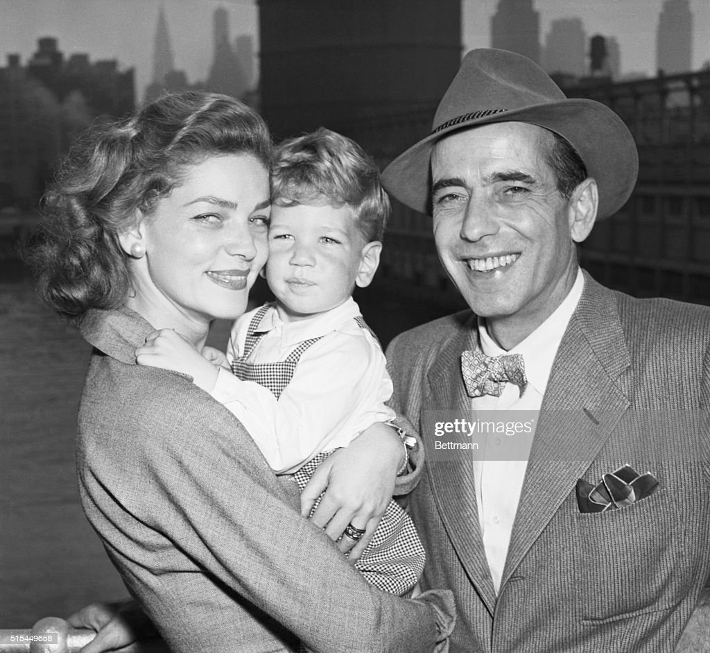 New York, NY- Actor Humphrey Bogart and his wife, actress Lauren Bacall, are just plain folks to their two-and-1/2-year-old son Stephen. They are arriving in New York from the French liner Ile De France. Bogart returned home after several months in Africa and England. His latest picture was filmed in Africa.