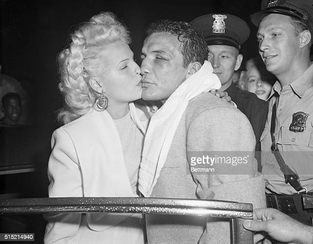 Detroit, MI- His face bruised and swollen from the blows of challenger Laurent Dauthuille, middleweight champ Jake La Motta relaxes to receive a...