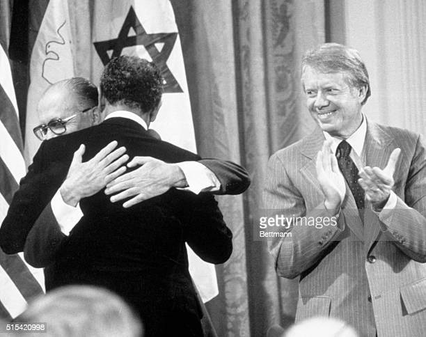 Washington, DC: - With Jimmy Carter applauding, Israeli Prime Minister Menachem Begin and Egyptian President Anwar Sadat embrace in the East Room of...