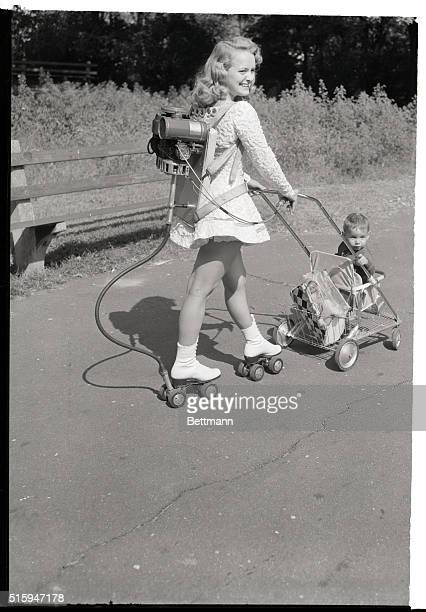 Really free wheeling Janet Slaughter moves along on her motorized roller skates while pushing 14monthold Arthur Mitchell in his baby buggy in Chicago...
