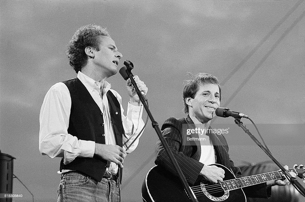 New York, New York- Art Garfunkel (l) and Paul Simon perform for more than 500,000 fans in Central Park 9/19. Police said the crowd was the largest to ever gather in the park. The concert marked the first ever time Simon and Garfunkel have appeared together in concert in 11 years. Garfunkel is shown singing while Simon is smiling into the audience.