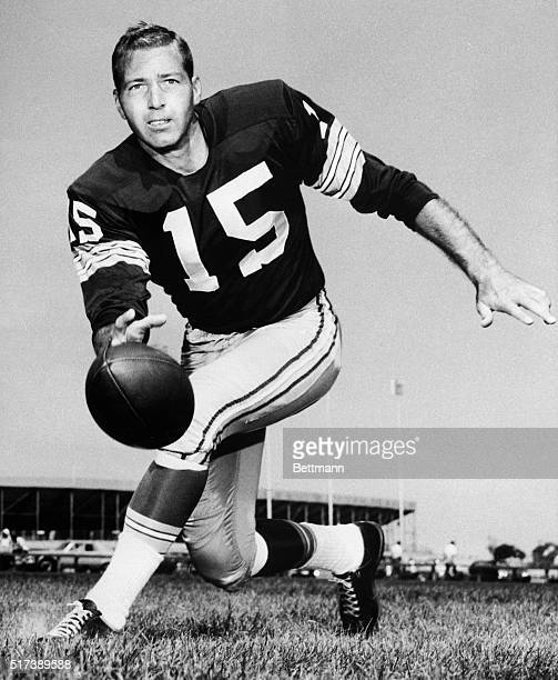 Bart Starr, quarterback for the Green Bay Packers, is shown throwing the ball while running.