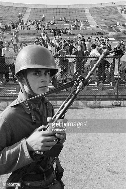 9/22/1973Santiago Chile An armed guard watches prisoners of the Chilean Army in the stands of Santiago's National Stadium The army is using the...