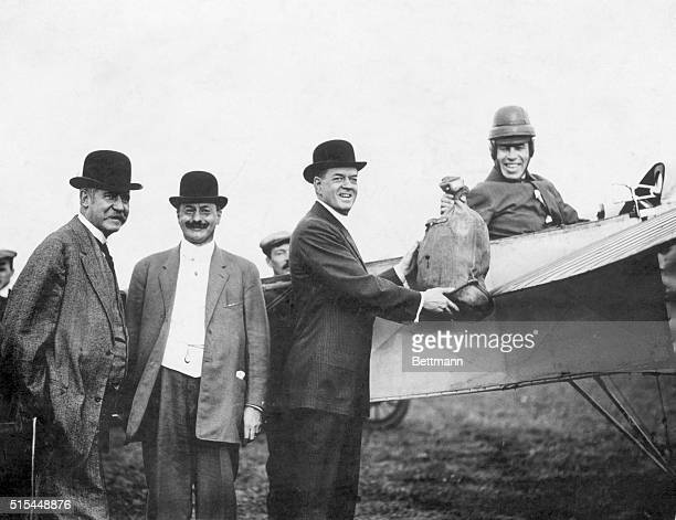 Early air mail delivery Left to right Postmaster of New York Morgan Superintendant Thixon and Postal Official Frank Hitchcock who accepts the sack of...