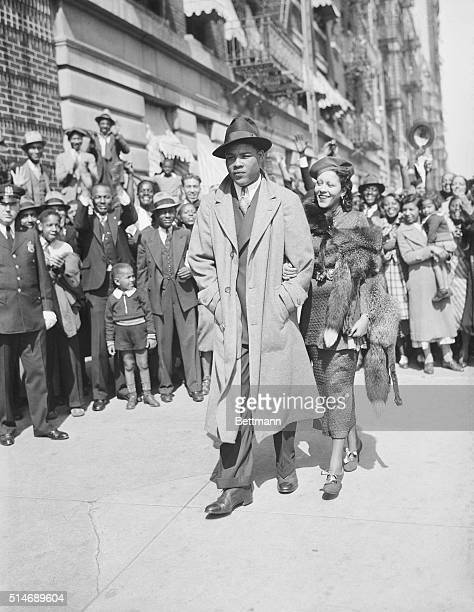 9/25/1935New York NY Joe Louis the 'Brown Bomber' of Detroit shown walking along a Harlem street with his bride the former Marva Trotter of Chicago...