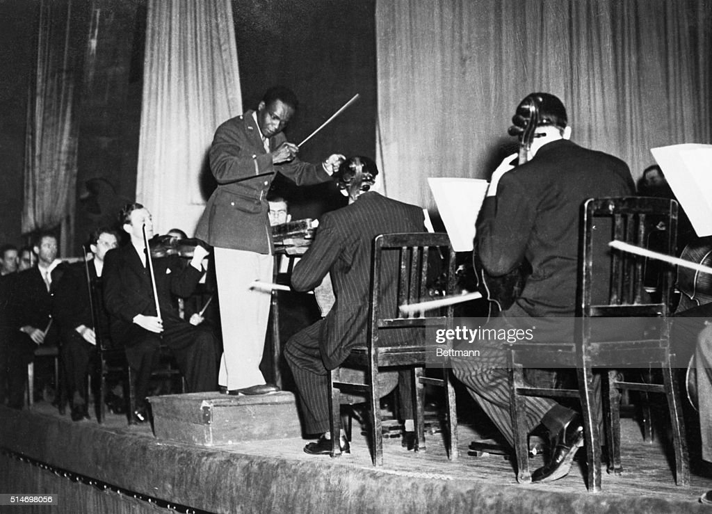 The Nazi racial predjudice suffered another blow recently when Rudolph Dunbar, brilliant American Negro conductor, led the Berlin Philharmonic orchestra at two concerts in Berlin's Titnaia Palast. Dunbar, Seen conducting during one of the concerts, will leave shortly for Paris where he will conduct a festival of American music in a series of four concert.