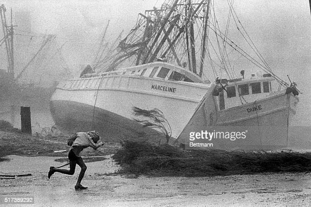 9/25/1967Brownsville Tx An adventurous sightseer braves heavy rains and blowing water for a closeup view of two shrimp boats aground near Port Isabel...