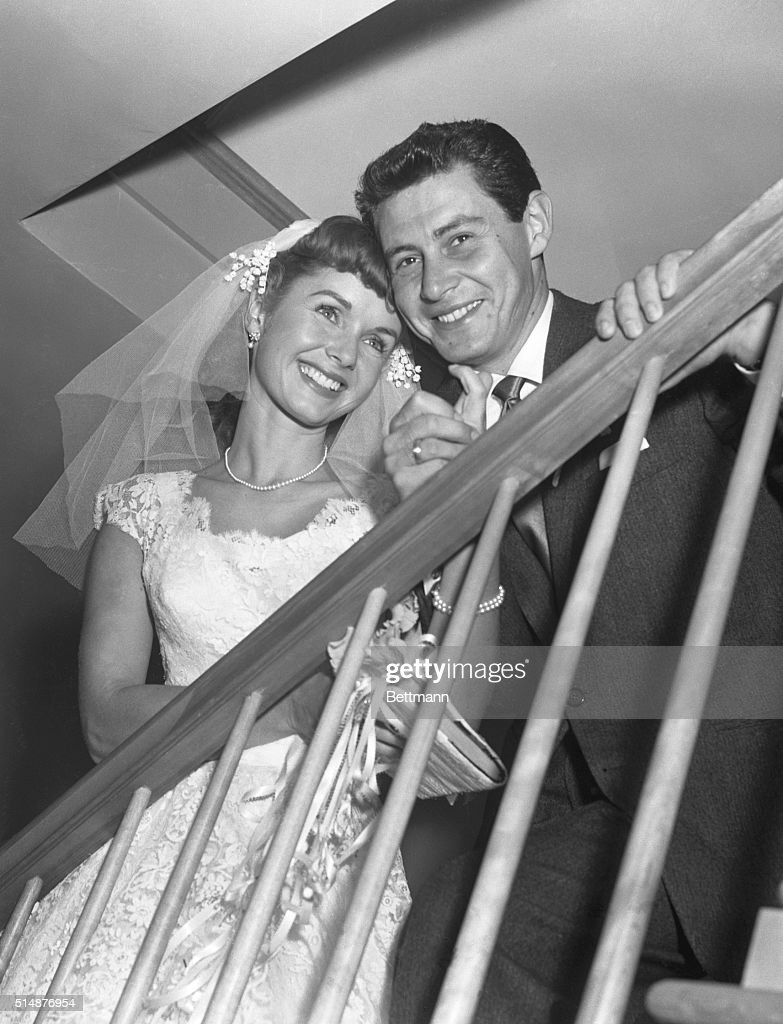 Singer Eddie Fisher and movie actress Debbie Reynolds, whose romance has been off and on on diverse occasions made it permanently when they were married late yesterday at Grossinger's Hotel in Ferndale. They were wed in a civil ceremony by Sullivan County Judge Lawrence Cook and are posing on the stairway here shortly after the ceremony.