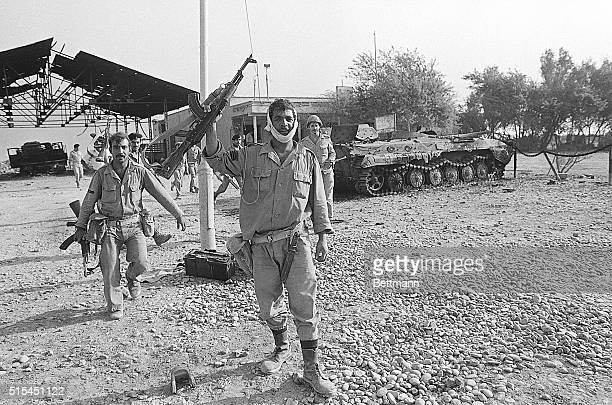 Shalamja, Iraqui-occupied Iran- Iraqi soldiers at this Iranian border checkpoint wave and carry AK47 automatic weapons, as they walk past a destroyed...