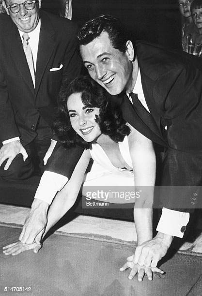 9/27/56Hollywood California Actress Elizabeth Taylor gets an assist from actor Rock Hudson as she plants her hands in cement in the lobby of...