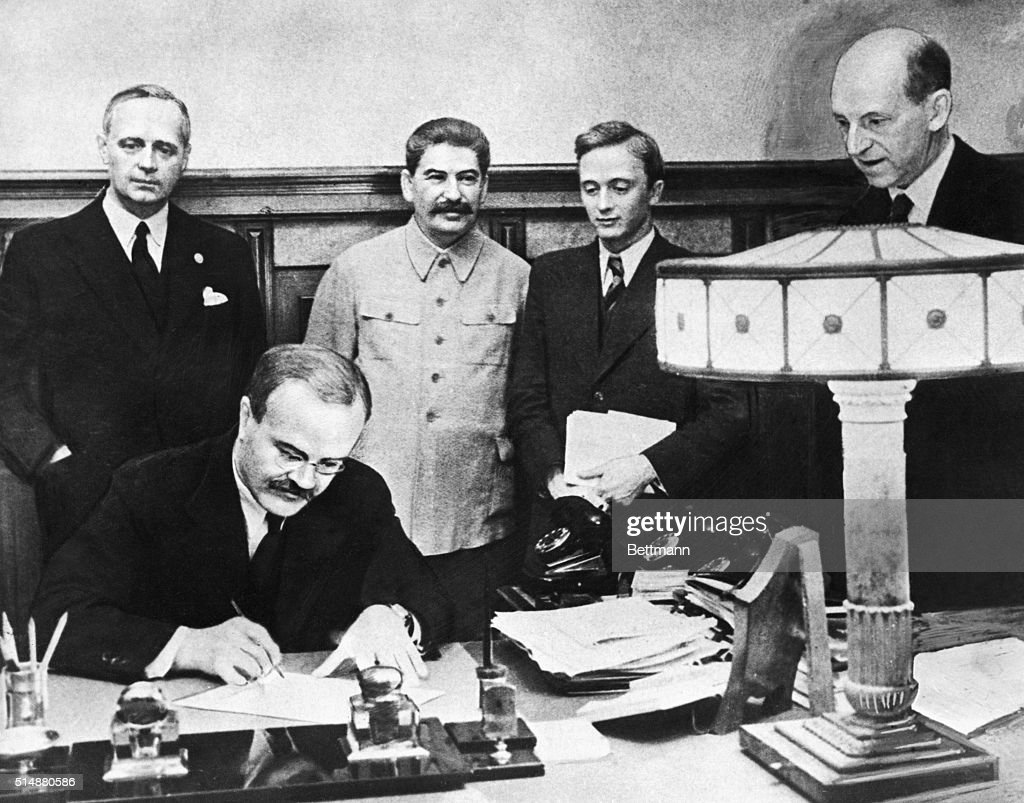 Signing of German Soviet treaty of friendship and determination of the frontier between the USSR and Germany on 9/28/1939. Shown are: M. Molotov signing the treaty. Standing left to right, Herr Joachim Von Ribentrop, Josef Stalin, V. Pavlov, and Herr F. Gaus.