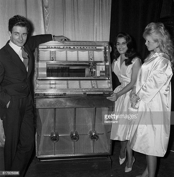 9/28/1959Paris France French actor Jacques Charrier poses with his wife actress Brigitte Bardot and singer Dalida in front of a juke box during the...