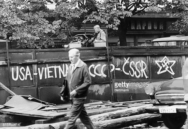 9/4/1968Prague Czechoslovakia A Russian soldier lights a cigarette as a Czech walks past a sign which equates US policy in Vietnam with the Soviet...