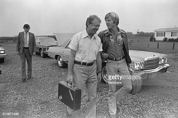 9/5/76Plains Georgia Democratic presidential hopeful Jimmy Carter carries actor Robert Redford's briefcase to a waiting plane at the local airport...