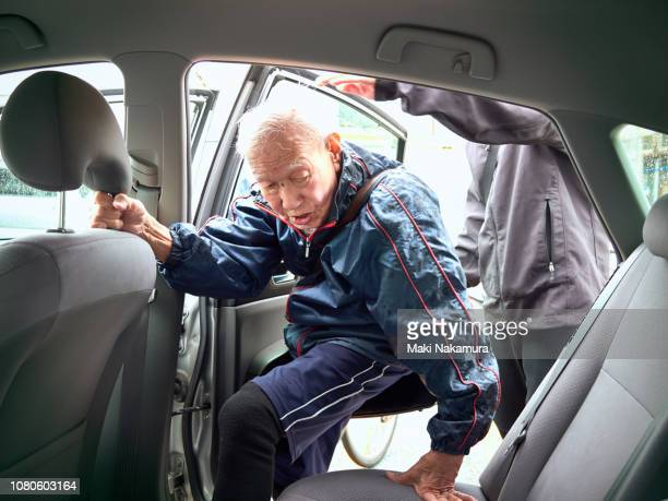 98-year-old senior male getting into a car.