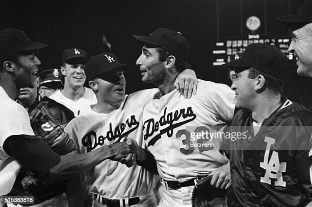 Dodger pitcher Sandy Koufax is mobbed by teammates on the field after pitching a perfect game Shown in the picture are Willie Davis Wes Parker Ron...