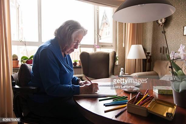 99-year-old senior woman coloring - lucy lambriex stockfoto's en -beelden