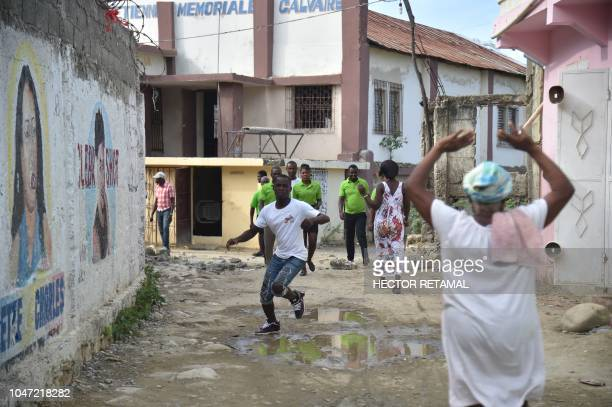Haitians react during the aftershock of an earthquake in the city of PortdePaix on October 7 2018 A 59magnitude earthquake struck off the northwest...