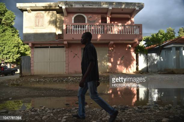 A man walks past a house damaged by an earthquake that hit the North of Haiti on October 6 in Gros Morne on October 8 2018 A 59magnitude earthquake...