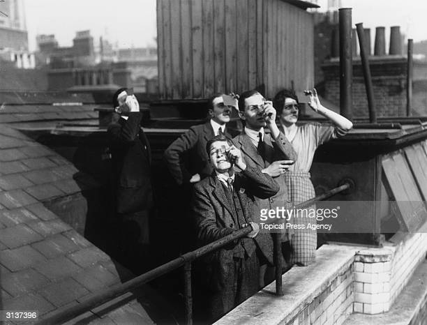 City workers viewing a solar eclipse from their office roof