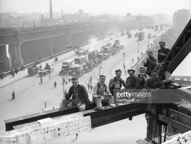 Workmen break for lunch on girders at Unilever House, Blackfriars, London.