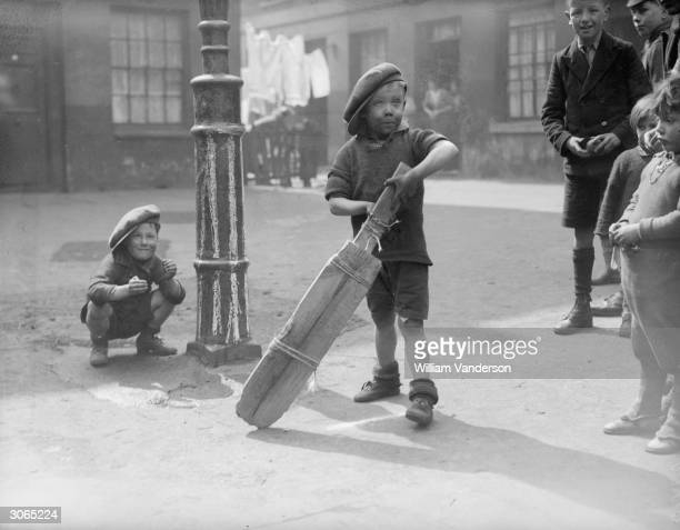 A group of children in a slum area of London's King's Cross play an improvised game of cricket with a lamppost as a wicket and a bat tied together...