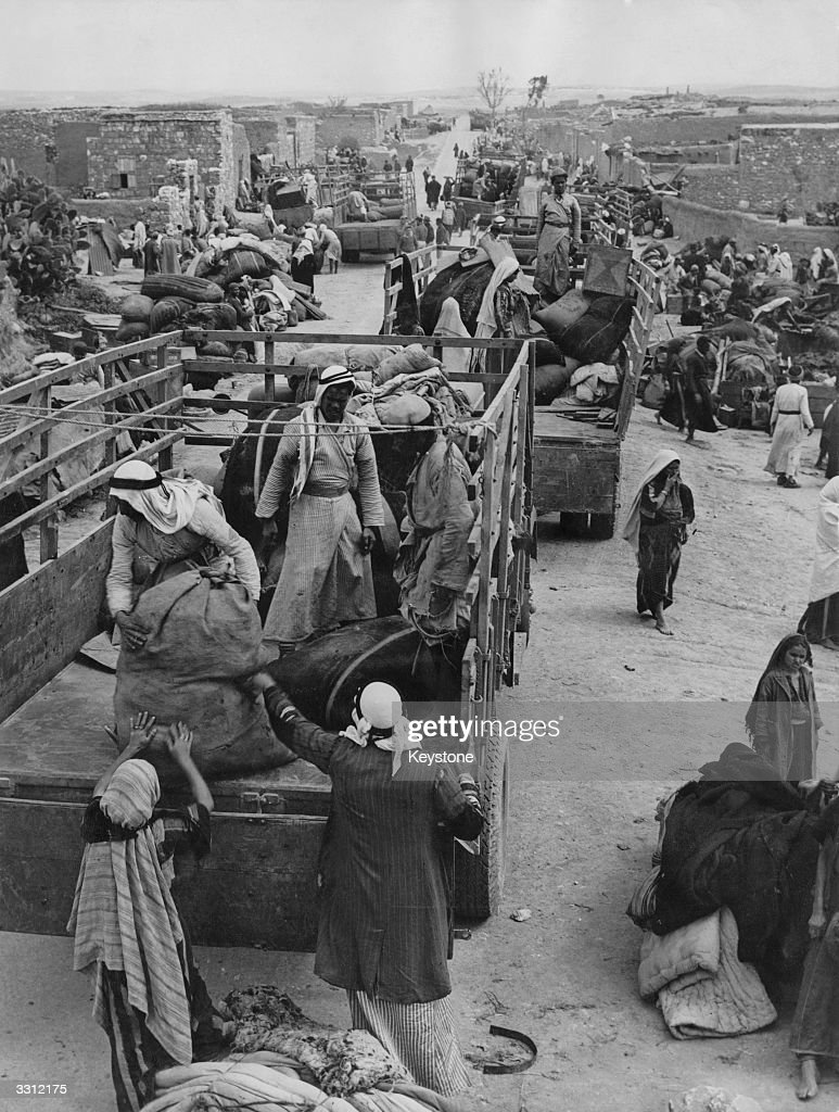 At the conclusion of the Armistice Agreement between Israel and Egypt, it was agreed that the Arab people in the Fellugah pocket who wished to cross into Arab territory would be allowed to do so. Arab belongings are accordingly loaded on to a convoy, with the village of Iraq Manshiya in the background.