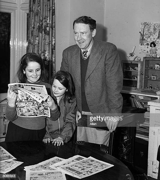 Labour Chancellor of the Exchequer Hugh Gaitskill at home with his daughters who are reading comics