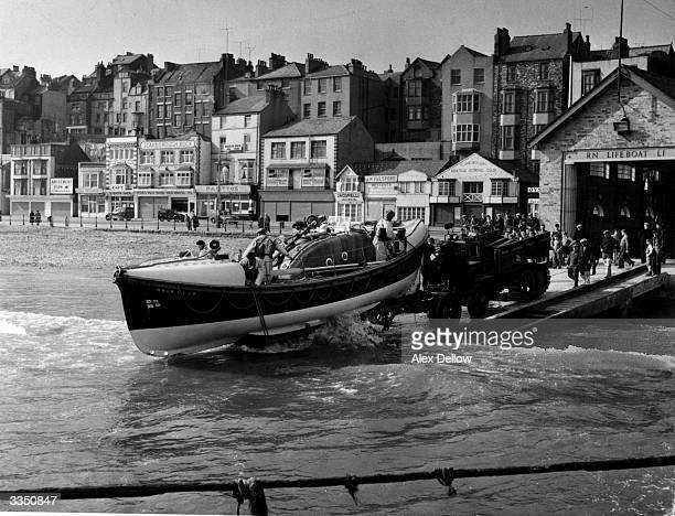 A tractor pushing the lifeboat down the slipway and into the sea at Scarborough England Original Publication Picture Post 7658 Saved From The Sea pub...