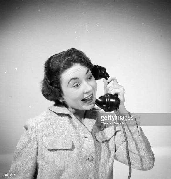 A woman modelling a jacket from Harrod's of London merrily fields a call