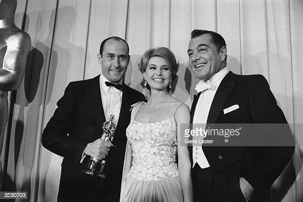 EXCLUSIVE LR American composer Henry Mancini American dancer Cyd Charisse and American actor Tony Martin pose backstage at the Academy Awards Santa...