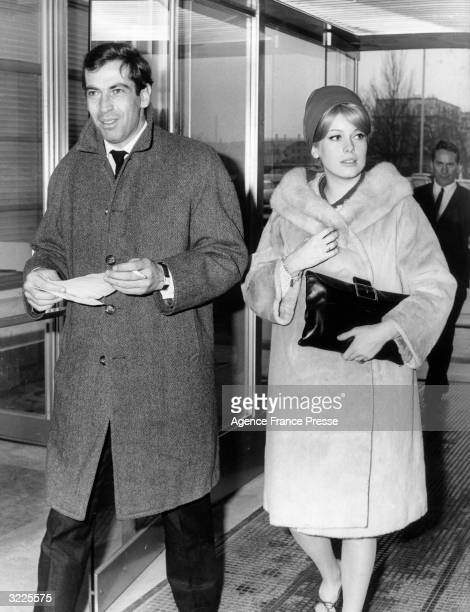 French director Roger Vadim and his girlfriend French actor Catherine Deneuve walking through an airport France They were on their way to Sweden for...