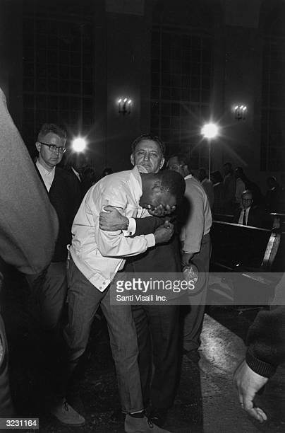 A Caucasian man in a suit grips the shoulders of an AfricanAmerican mourner bent over with his hand to his face at the funeral of Dr Martin Luther...