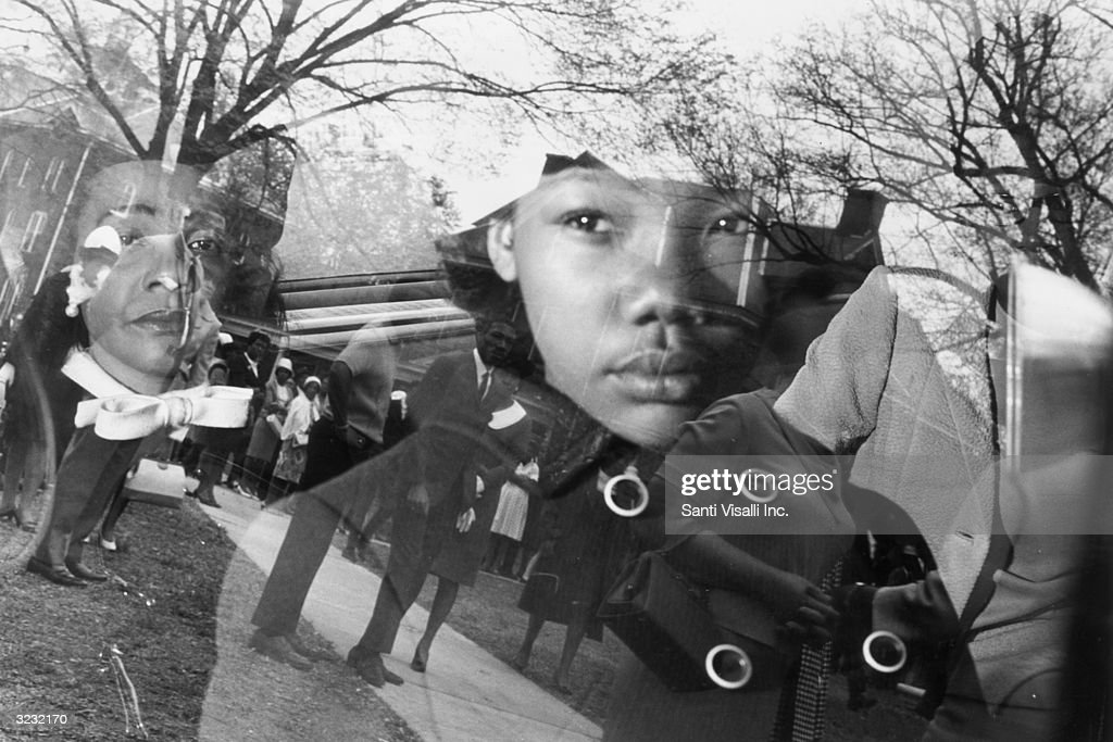 Coretta Scott King, widow of Dr. Martin Luther King Jr (1929 - 1968), and her daughter, Yolanda, sit in a car as it leaves for Martin Luther King Jr's funeral, Atlanta, Georgia. The reflection of a group of mourners standing in front of a house is visible in the window of the car.