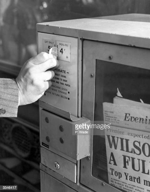 Placing money into a coin-operated vending machine selling newspapers in Kensington High Street, London.