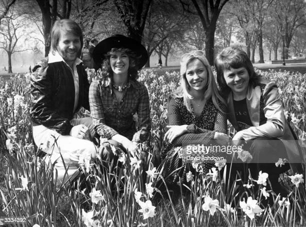 Swedish pop group Abba Benny Andersson AnniFrid Lyngstad Agnetha Faltskog and Bjorn Ulvaeus sitting amongst the daffodils in London following their...