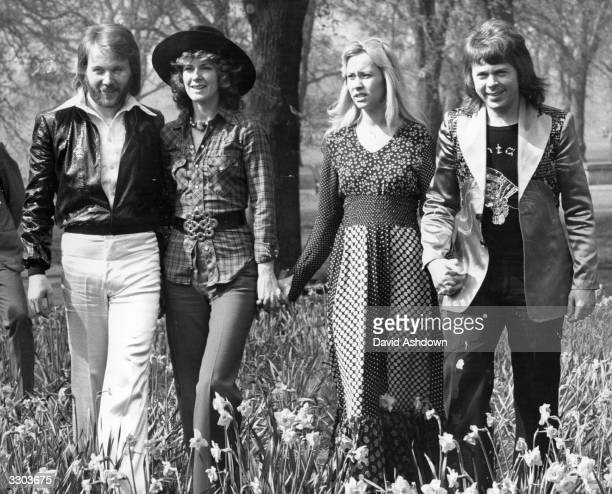 Swedish pop group Abba winners of the 1974 Eurovision Song Contest at Brighton strolling hand in hand amongst the daffodils in Hyde Park London
