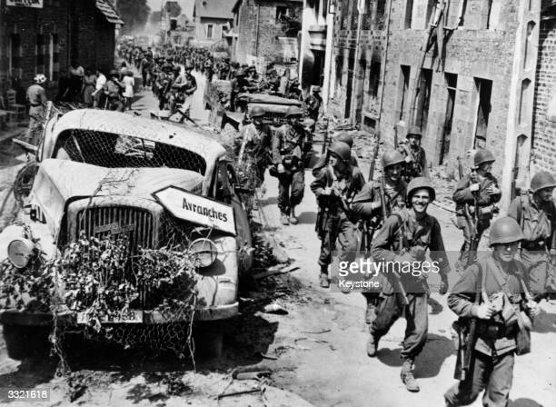 US infantrymen make their way past a wrecked German truck on the way to Avranches during the Allied invasion of Normandy