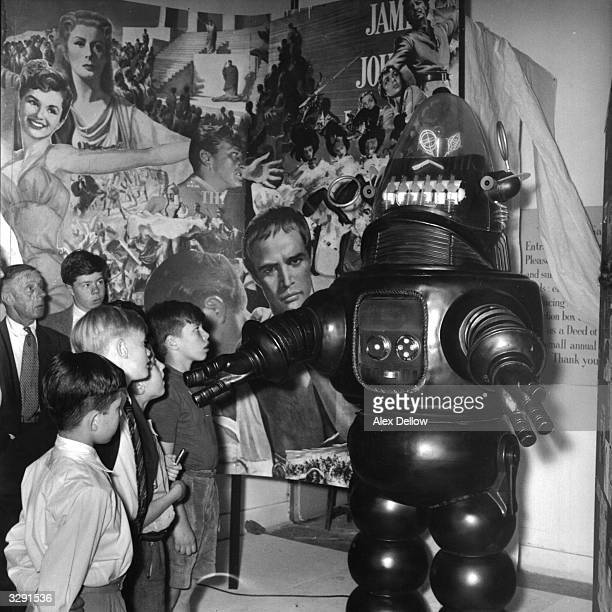 A display featuring movie and television character Robbie The Robot from 'Forbidden Planet' enthralling a group of youngsters Original Publication...