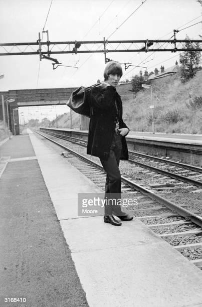 Radio Caroline disc jockey Johnnie Walker waiting at a railway station.