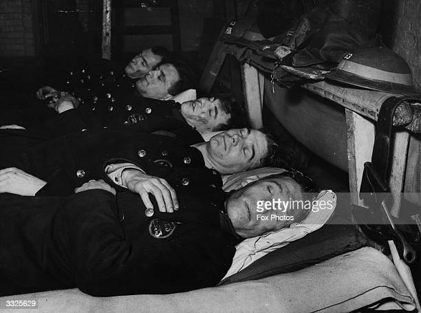 After 12 hours fire fighting during the London blitz firemen enjoy a sleep but keep on their uniform