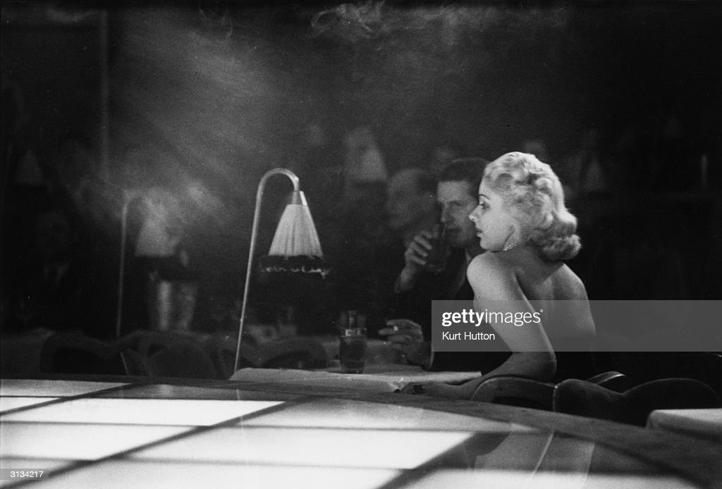 A couple sitting next to the stage for a floor show at 'La Nouvelle Eve', the newest and most expensive night spot in Paris. Original Publication: Picture Post - 5214 - Deux Jolies Anglaises - pub. 1950