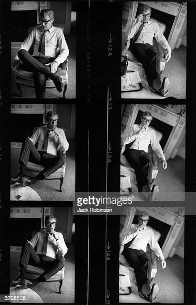 Contact sheet showing a series of photographs of British actor Michael Caine sitting in an armchair smoking a cigarette reading and talking in an...