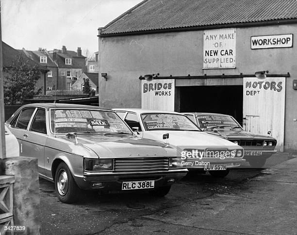 Second hand cars for sale outside a garage