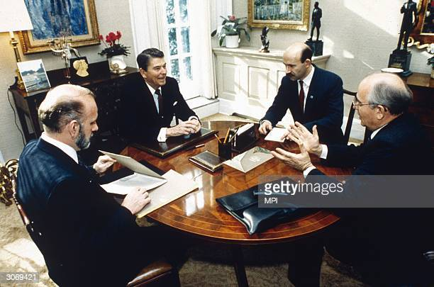 United States President Ronald Reagan engages in animated discussion with his ArmsControl team and a Soviet official in the private study beside the...