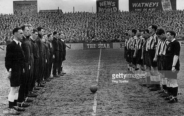 Fulham and Newcastle United football teams observe a minutes silence before the start of a match in memory of the late King George VI