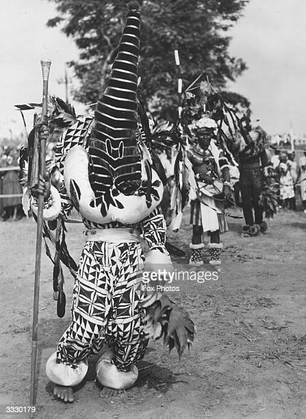 A witch doctor in full regalia carrying a silvertopped cane in Nigeria
