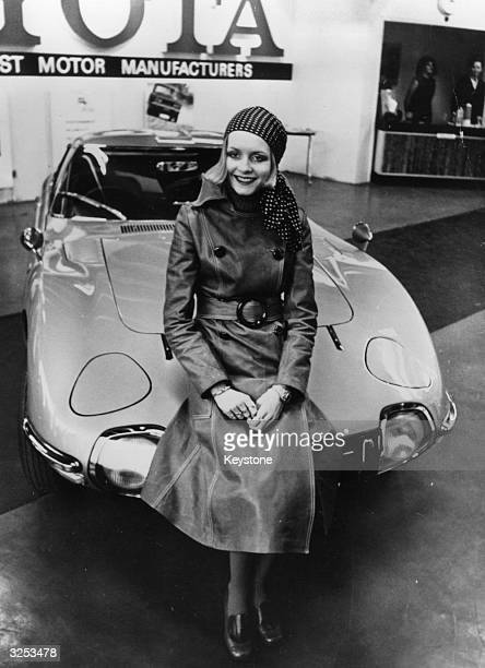 British fashion model and singer Twiggy sitting on a Toyota 200 GT car