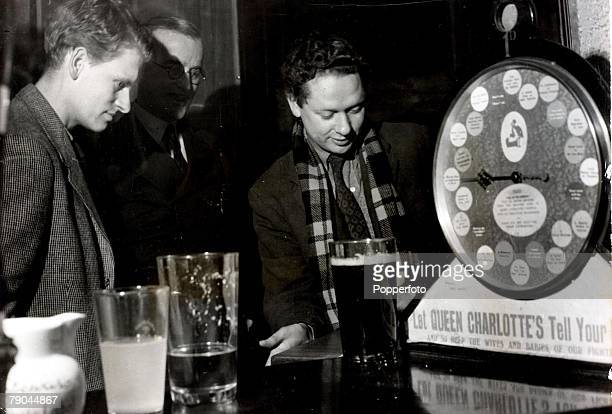9th January 1946 A picture of Welsh poet Dylan Thomas enjoying a game of shovehalfpenny in his Chelsea local
